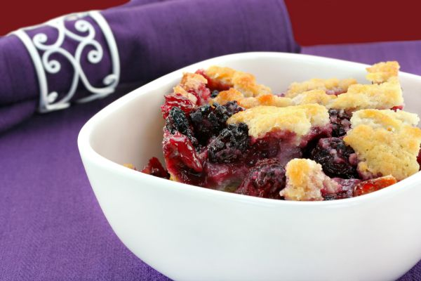 Berry cobbler, freshly made, in a white bowl.